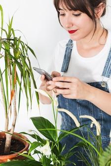 Hermosa mujer joven con teléfono móvil cerca de plantas en maceta