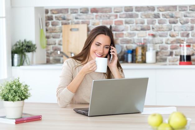 Hermosa mujer joven con teléfono móvil y una computadora portátil en la cocina.