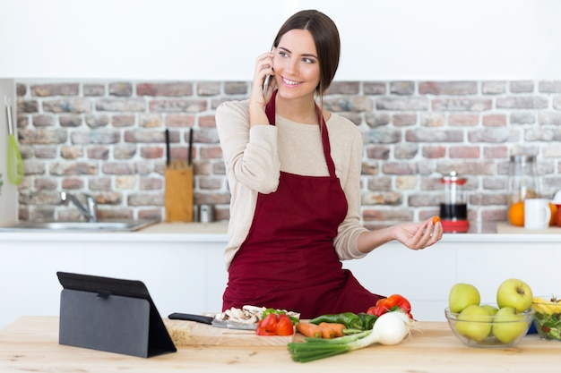 Hermosa mujer joven con teléfono móvil mientras se cocina en la cocina.