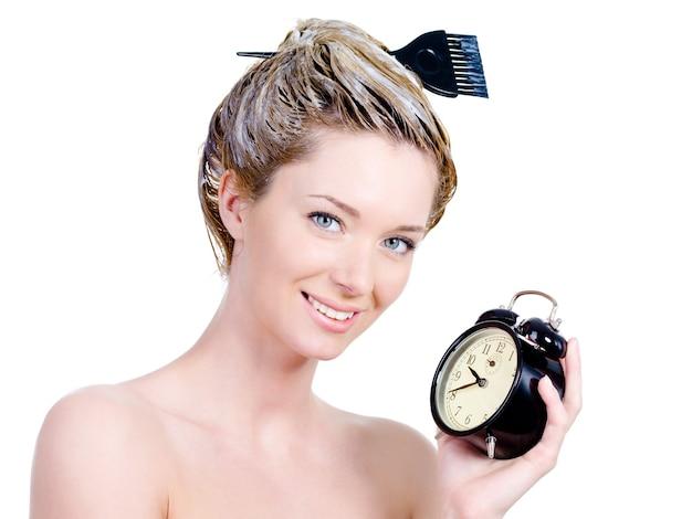 Hermosa mujer joven con tinte para el cabello en la cabeza esperando un tiempo aislado en blanco