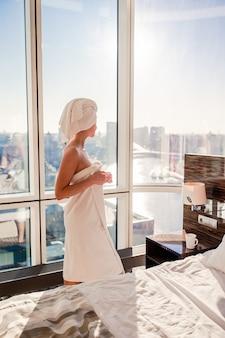Hermosa mujer joven en una toalla de baño blanca en la cabeza relajante después de la ducha en la cama con una taza de café