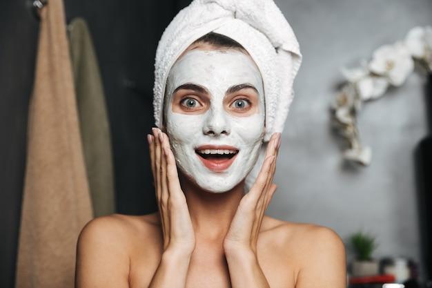 Hermosa mujer joven con una toalla envuelta alrededor de su cabeza aplicando mascarilla en el baño