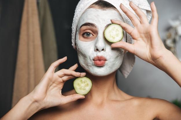 Hermosa mujer joven con una toalla envuelta alrededor de su cabeza con mascarilla