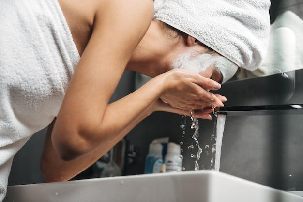 Hermosa mujer joven con una toalla envuelta alrededor de su cabeza quitando la mascarilla con agua en el baño