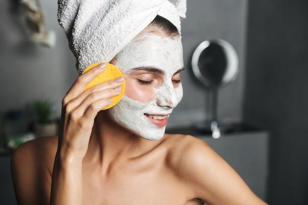 Hermosa mujer joven con una toalla envuelta alrededor de su cabeza quitando la mascarilla con una esponja en el baño