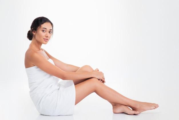 Hermosa mujer joven en toalla sentada en el suelo