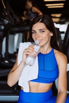 Hermosa mujer joven con una toalla sobre su hombro bebiendo agua de una botella en el gimnasio
