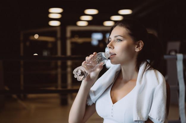 Hermosa mujer joven con una toalla sobre sus hombros bebiendo agua de una botella en el gimnasio