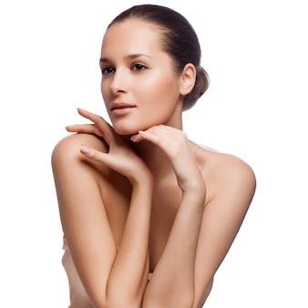 Hermosa mujer joven tocando su cara. piel sana fresca