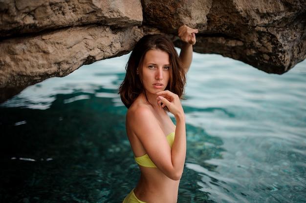Hermosa mujer joven en traje de baño amarillo de pie en agua de mar azul cerca de la roca