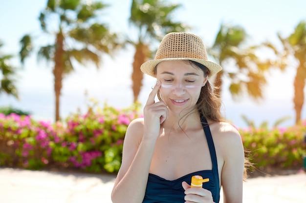Hermosa mujer joven en traje de baño aplicando crema solar