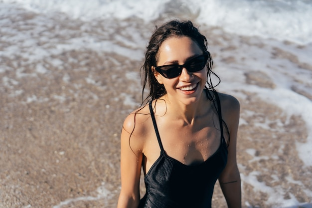 Hermosa mujer joven en traje de baño mojado negro