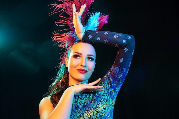 Hermosa mujer joven en traje de carnaval y mascarada en coloridas luces de neón en pared negra