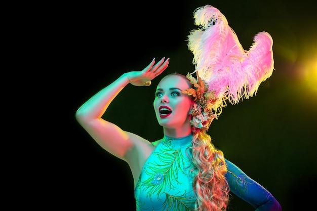 Hermosa mujer joven en traje de carnaval y mascarada en coloridas luces de neón sobre negro