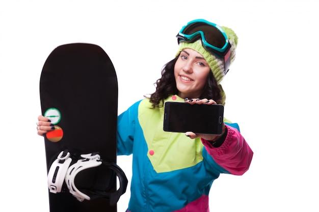 Hermosa mujer joven en traje de esquí y espera snowboard