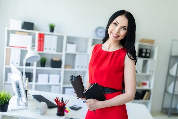 Hermosa mujer joven en un traje rojo está de pie en la oficina y está sosteniendo un cuaderno y un vaso de café.