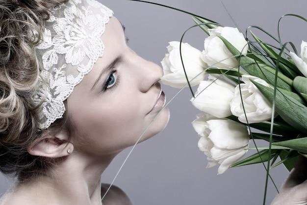 Hermosa mujer joven con tulipanes blancos