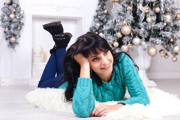 Hermosa mujer joven tumbada en el suelo en el interior en un interior de navidad