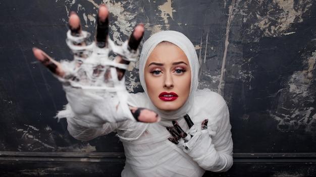 Hermosa mujer joven en vendajes. chica en traje de momia, tirando de la mano.