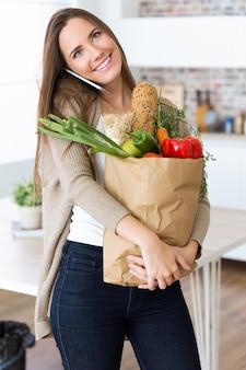 Hermosa mujer joven con verduras en bolsa de compras en casa.