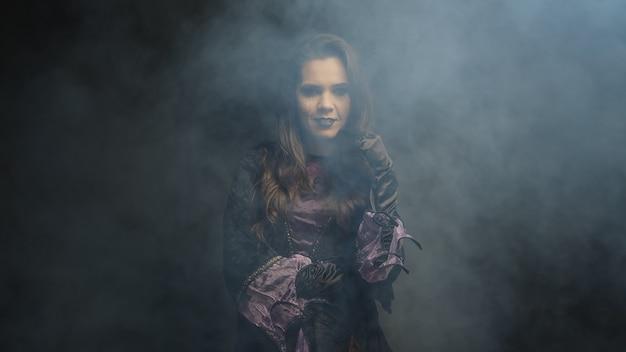 Hermosa mujer joven vestida como una bruja para halloween sobre fondo negro.