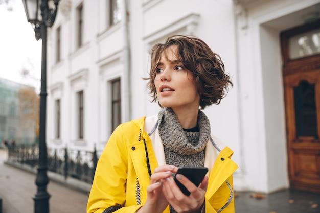 Hermosa mujer joven vestida con impermeable chateando