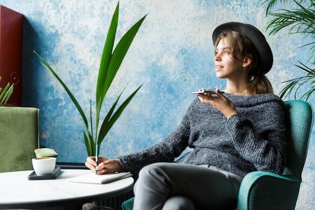 Hermosa mujer joven vestida con suéter y sombrero sentado en una silla en la mesa de café, hablando por teléfono móvil, interior elegante, tomando notas