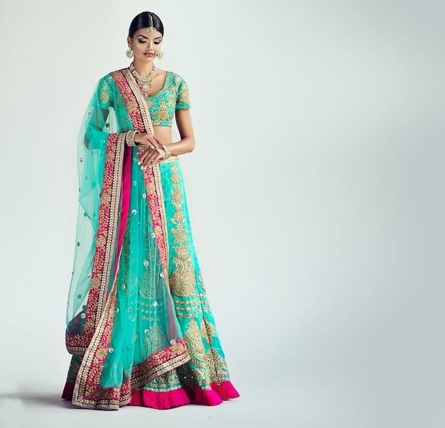 Hermosa mujer joven vestida con traje nacional indio sari y conjunto de joyas retrato en alto