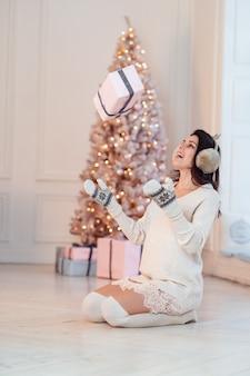 Hermosa mujer joven con un vestido blanco arroja un regalo