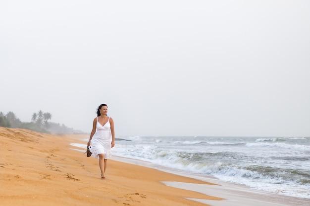 Hermosa mujer joven en vestido blanco caminando por la playa de arena