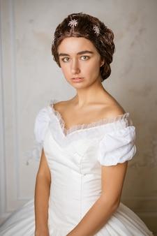 Hermosa mujer joven con un vestido blanco y un hermoso peinado, imagen romántica