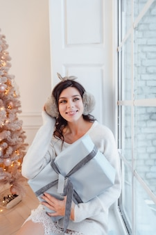 Hermosa mujer joven en vestido blanco posando con caja de regalo