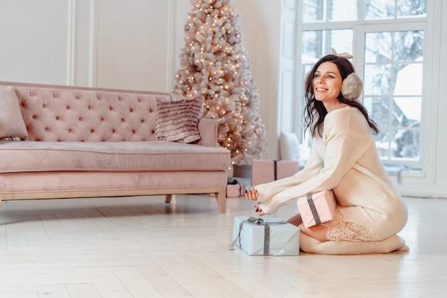 Hermosa mujer joven en vestido blanco posando con cajas de regalo