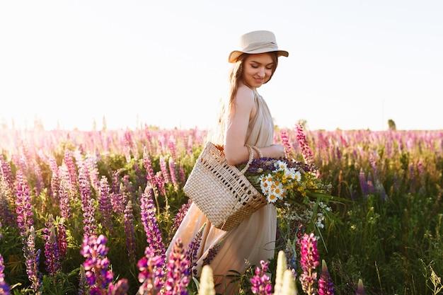 Hermosa mujer joven en vestido blanco y sombrero de paja caminando en campo de flores