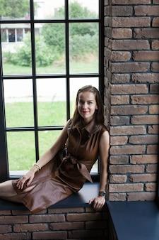 Hermosa mujer joven en vestido de cuero marrón se sienta en el alféizar de la ventana