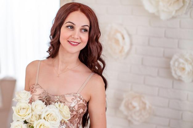 Hermosa mujer joven en un vestido dorado, con un ramo de rosas blancas se ve lejos.