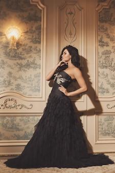 Hermosa mujer joven con vestido hermoso está posando junto a la pared antigua