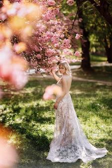 Hermosa mujer joven en vestido largo de lujo cerca del florecimiento de sakura. chica elegante cerca de flores de sakura floreciente en el parque de la primavera. armonía con el concepto de naturaleza.