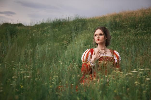 Hermosa mujer joven con un vestido medieval rojo largo está sentada en la hierba en el campo