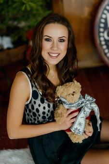 Hermosa mujer joven en vestido en navidad interior con un oso de peluche en sus brazos y sonriendo. concepto de vacaciones de navidad y año nuevo.