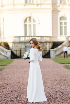Hermosa mujer joven en vestido de novia posando en la calle en la ciudad