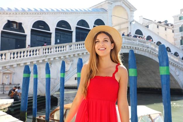 Hermosa mujer joven con un vestido rojo está de pie frente al famoso puente de rialto en venecia, italia