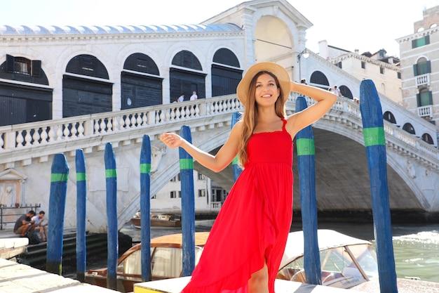 Hermosa mujer joven con vestido rojo en venecia, italia
