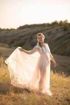 Hermosa mujer joven en vestido rosa aire posando en el campo