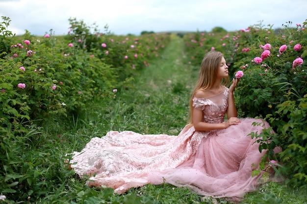 Hermosa mujer joven con un vestido rosa con pelo largo y rizado posando junto a rosas en un jardín.