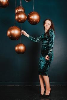 Hermosa mujer joven en un vestido de terciopelo azul verde, posando