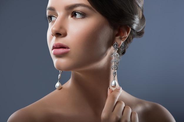 Hermosa mujer con joyas preciosas en estudio