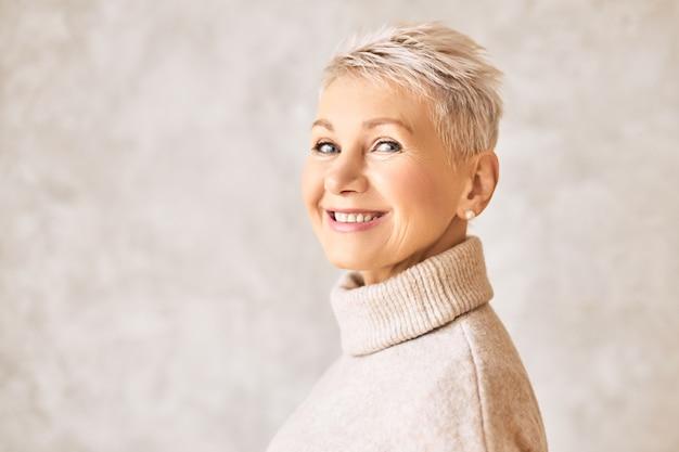 Hermosa mujer jubilada feliz vistiendo suéter acogedor y peinado corto