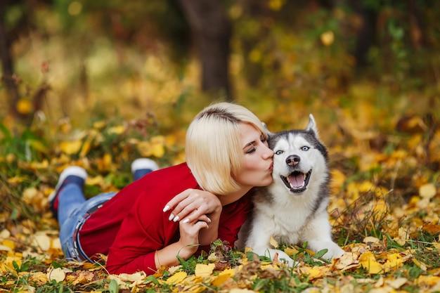 Hermosa mujer juega con perro husky en bosque otoñal