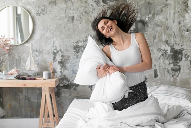 Hermosa mujer jugando con almohada